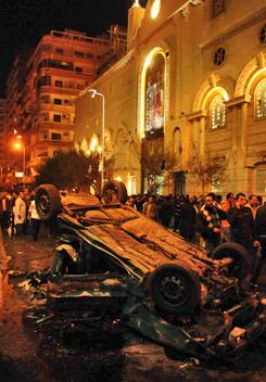 Egyptians inspect the site of a car bomb attack on a Christian church in Alexandria on Saturday.
