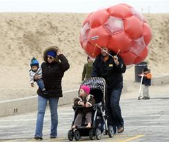 Lora, second left, and Jordi Arago, right, and their children Pau and Alex of Seal Beach, Calif., leave the beach as rain begins to fall Sunday morning.