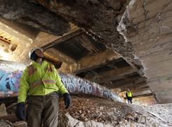 "Civil engineers Harry Smeltzer Sr. and Will Lynes, of the Pennsylvania Department of Transportation, inspect Heth's Run Bridge in Pittsburgh. The bridge was built in 1914. An $11 million planned upgrade could make use of ""orphan earmark"" funds that are held up on other projects."