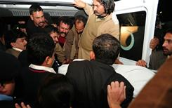 Activists of ruling Pakistan People's Party lift the body of Punjab governor Salman Taseer in an ambulance in Islamabad on Tuesday. Taseer was shot dead near his home in a political assassination that threatens to sink the nuclear-armed country deeper into chaos.