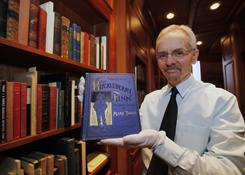 Mark Twain archivist Mark Woodhouse holds a first edition of Adventures of Huckleberry Finn at the Mark Twain Archive at Elmira College in Elmira, N.Y. The book has been a target of criticism since it was first published in 1885.