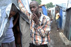 Joel Sainton visits Silly Remercile and her two small children in their tent in Carrefour, Port-au-Prince.