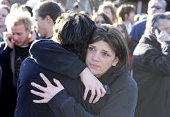 A student is united with a loved one Wednesday outside Millard South High School, in Omaha, after police say a student shot two administrators before fatally shooting himself.