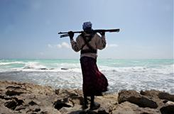 An armed Somali pirate stands along the coastline while the Greek cargo ship, MV Filitsa, is seen anchored just off the shores of Hobyo town in northeastern Somalia, where it was being held by pirates in January 2010.