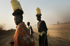 Women walk to their village with water on the outskirts of the southern Sudanese city of Juba on Thursday. South Sudan, one of the world's poorest countries, is preparing for an independence referendum Sunday following a historic 2005 peace treaty that brought an end to decades of civil war between the Arab north and predominantly Christian and animist south.