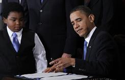 President Obama signs the health care reform bill last year in Washington. Marcelas Owens, of Seattle, looks on.