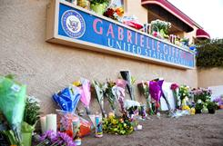 Flowers and candles are piled outside the office of Rep. Gabrielle Giffords after Giffords was shot in the head by a gunman who opened fire outside a grocery store Saturday in Tucson.