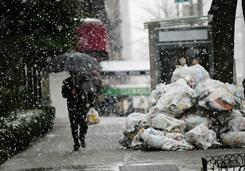 A man walks past a trash pile as fresh snow falls over Manhattan in New York on Friday.