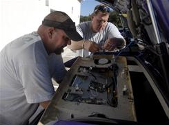 Rich Potts, left, and Palumbo put a television and speakers into the back of Tom Palumbo's Dodge Magnum in Melbourne, Fla.
