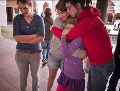 Nadine Heiden, 16, left, Stella Chavin, 17, Marilyn Hill, 12, and Ally Tanzillo, 19, comfort each other at a memorial in downtown Tucson Sunday for Rep. Gabrielle Giffords, D-Ariz., and other victims of Saturday's shooting.