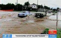 Vehicles plow through floodwaters in the city of Toowoomba on Tuesday. Heavy rain across southeast Queensland will hamper search and rescue efforts for dozens of people who are missing or stranded.