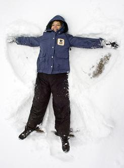 U.S. postal carrier MaryAnn Blaxton creates snow angels in the empty post office parking lot in Decatur, Ala., on Monday. Blaxton came to work only to discover the post office was closed for the day.