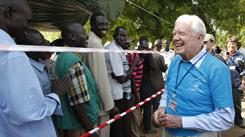Former president Jimmy Carter greets Southern Sudanese men waiting to vote Sunday in Juba, Southern Sudan.