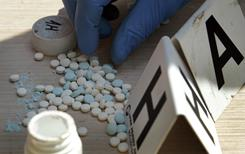 A police officer counts pills containing pseudoephedrine during a raid at a suspected meth house in Gerald, Mo.