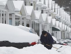 Glenn Humphreys clears snow in front of his house in Albany, N.Y., on Wednesday.