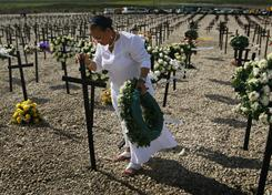 Fradzelle Wiener prepares to place a wreath on a cross during a ceremony Tuesday honoring the tens of thousands buried in a mass grave at Titanyen, outside Port-au-Prince, Haiti.