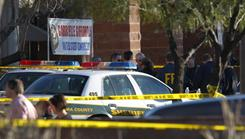 Officers secure the scene of a shooting Saturday outside a Safeway store in Tucson. Rep. Gabrielle Giffords, a third-term Democrat, was critically wounded.