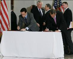 House Majority Leader Eric Cantor, R-Va., and House Speaker John Boehner, R- Ohio, sign a condolence and well wishes book for the victims of the mass shooting in Arizona on Capitol Hill on Wednesday.