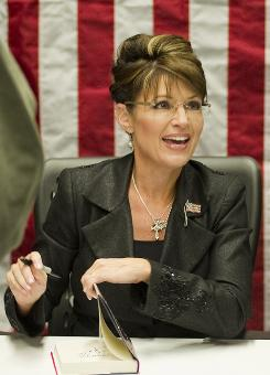 Sarah Palin, pictured signing copies of her book on Nov. 30, responded to critics on Tuesday that she bore some responsibility for the assassination attempt on Rep. Gabrielle Giffords, D- Ariz.