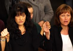 Roxanna Green, left, attends a Mass for shooting victims on Tuesday at St. Odilia Catholic Church in Tucson. Green's daughter, Christina-Taylor, died in Saturday's attack.