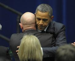 President Obama hugs Mark Kelly, husband of Rep. Gabrielle Giffords, after speaking at a memorial service for victims of Saturday's mass shooting in Tucson.
