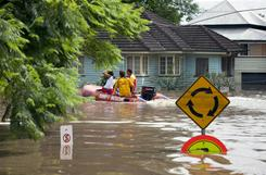 "A Sunshine Coast surf rescue boat patrols through floodwaters in the streets of the Rosalie area of Brisbane on Thursday. Australia's third-largest city Brisbane was turned into a ""war zone"" on Thursday with whole suburbs under water and infrastructure smashed as the worst flood in decades hit 30,000 properties."