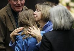 "Shooting victim Pam Simon, right, hugs attendees at Wednesday's ""Together We Thrive"" services for the victims in Tucson."