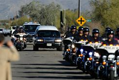 A hearse carrying the casket of U.S. District Court Judge John Roll passes in front of St. Elizabeth Ann Seton church for a funeral service Friday in Tucson.