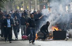 Demonstrators throw stones at police during clashes in Tunis, Jan. 14, 2011. Tunisia's president declared a state of emergency and announced that he would fire his government as violent protests escalated.