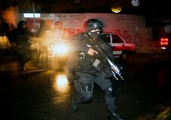 A state police officer runs during a confrontation with members of a gang in the neighbourhood of Casa Blanca in Xalapa, State of Veracruz, Mexico, on Thursday.