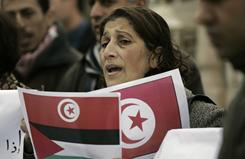 A Palestinian woman holding printed Tunisian and Palestinian flags takes part in a demonstration of solidarity with the Tunisian people in front of the Tunisian Embassy in the West Bank city of Ramallah on Saturday.