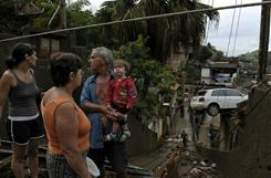 A family looks around their destroyed house Saturday in an area affected by a mudslide. Dozens of victims may still buried in the Morro do Dede neighborhood in Nova Friburgo, north of Rio de Janeiro.