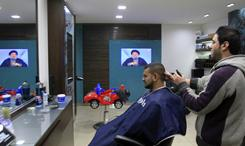A hairdresser listens to the speech of Hezbollah leader Hassan Nasrallah in the southern port city of Sidon, Lebanon, on Sunday. Nasrallah made his first public comments since ministers from his movement and their allies resigned from the Cabinet on Wednesday, toppling the Western-backed government.