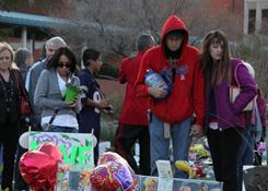 Mourners stop Sunday at a makeshift memorial in front of University Medical Center in Tucson
