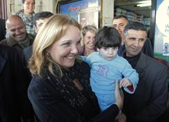 Josette Sheeran, head of the World Food Program, holds a toddler as she stands outside a shop in the West Bank city of Hebron on Monday. Sheeran toured Hebron to inspect the distribution of food through electronic vouchers, a program that agency officials say was first tried out in the West Bank.