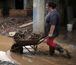 A woman pushes a cart containing belongings recovered from her house damaged after landslides in Nova Friburgo, Brazil, Tuesday. Brazil's army on Monday sent some 700 soldiers to help throw a lifeline to desperate neighborhoods that have been cut off from food, water or help in recovering bodies since mudslides killed at least 665 people.