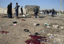 Iraqi onlookers and policemen inspect the spot where a suicide bomber blew himself up Tuesday, killing 50 among a crowd of police recruits in Tikrit.