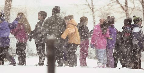 Students wait in the snow to be let in after recess in Minnesota.