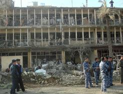 Members of Iraq's security forces gather next to the ruins of the Baquba headquarters of the Force Protection Service (FPS) on Wednesday. A suicide bomber attacked with an ambulance packed with explosives.