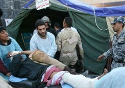 Iraqi paramedics wheel an injured man into a Karbala hospital emergency room Thursday.