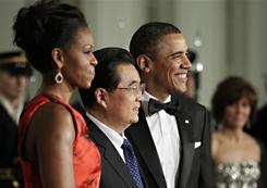 President Barack Obama, right, and first lady Michelle Obama, left, are photographed as they welcome China's President Hu Jintao, center, to the state dinner on the North Portico of the White House on Wednesday.
