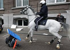 A demonstrator protects himself with his placard after police on horseback dispersed protesters outside parliament following a student rally against planned government cuts to higher education and increases in tuition fees,