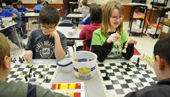 Sam Peterson, left, and Erin Mallo, both 11, play a game with members of the Sartell Middle School chess club on Jan. 18.