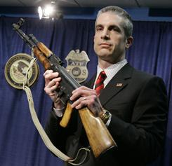 Law enforcement official Andrew Traver displays an assault weapon from a confiscated cache Feb. 28, 2007, in Chicago.