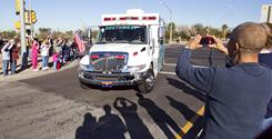 Well-wishers wave and take photos of the ambulance carrying Rep. Gabrielle Giffords during her transfer Friday to a Houston rehabilitation center.
