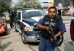 A municipal police officer confronts members of a gang in Acapulco, Mexico, on Jan. 8, where 15 decapitated bodies were left in front of a shopping center.