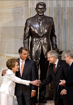 Former first lady Nancy Reagan shakes hands with Senate Majority Leader Harry Reid of Nevada in the Capitol Rotunda on on June 3, 2009. Rep. John Boehner stands next to her.