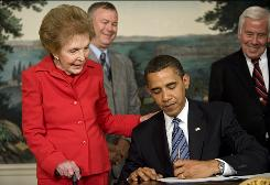 President Obama signs the Ronald Reagan Centennial Commission Act on June 2, 2009, as former first lady Nancy Reagan looks on.