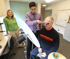 Wounded veteran Patrick Horan works with Dr. Bryce B. Appelbaum as Horan's wife, Patty, looks on Tuesday during vision therapy in Bethesda, Md.