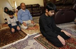 "Umaid Qureshi, 14, leads a prayer for his family in Herndon, Va. ""If Americans get to know Muslims, there won't be any issues,"" says his father, Wajahat."